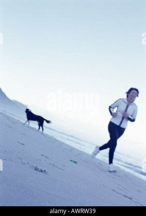Mature woman running on beach, dog in background - Stock Photo