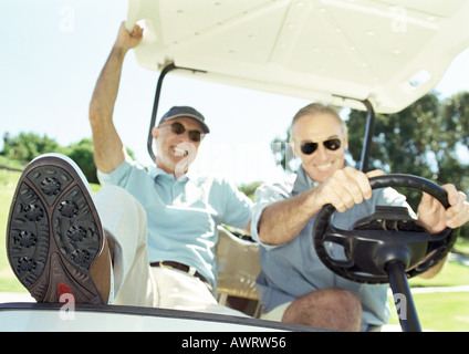 Two mature men in golf cart, smiling, close-up - Stock Photo