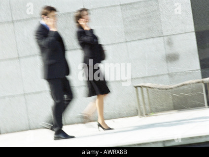 Businessman and woman using cell phones in street, full length, blurred motion - Stock Photo