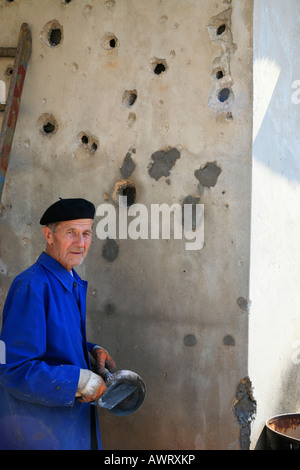 Bosnian man fills bullet holes left in his house from the war, Sarajevo - Stock Photo