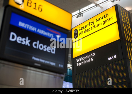 Security Notice and fast bag drop desk closed sign at London Heathrow Airport Terminal 5 - Stock Photo