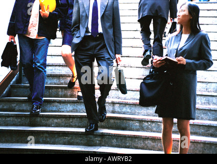 Businesswoman taking notes in front of stairs - Stock Photo