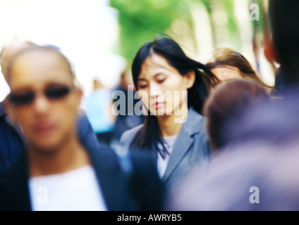 Businesswoman in crowd, head and shoulders, blurred - Stock Photo