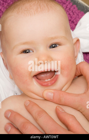 mother showing off her 6 month old baby girl showing first teeth - Stock Photo