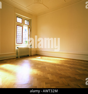 PR SUNNY EMPTY ROOM WITH OAK WOODEN FLOORING AND ONE STAINED GLASS WINDOW - Stock Photo