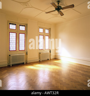 PR SUNNY EMPTY ROOM WITH OAK WOODEN FLOORING AND TWO STAINED GLASS WINDOWS - Stock Photo