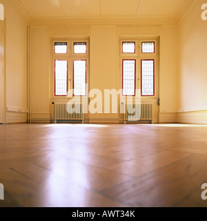 PR EMPTY ROOM WITH OAK WOODEN FLOORING AND TWO STAINED GLASS WINDOWS - Stock Photo