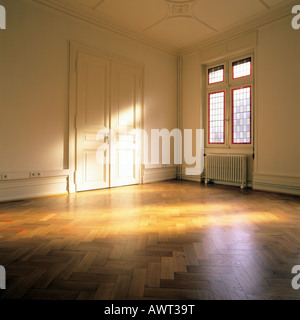 PR SUNNY EMPTY ROOM WITH OAK WOODEN FLOORING CLOSED DOOR AND ONE STAINED GLASS WINDOW - Stock Photo