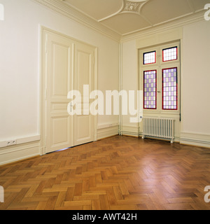 PR EMPTY ROOM WITH OAK WOODEN FLOORING CLOSED DOOR AND A STAINED GLASS WINDOW - Stock Photo