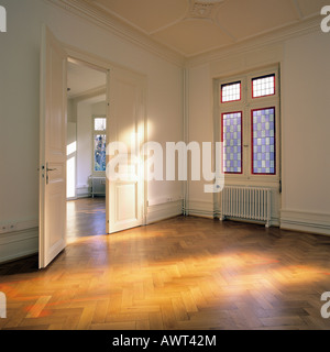 PR SUNNY EMPTY ROOM WITH OAK WOODEN FLOORING DOOR OPEN AND ONE STAINED GLASS WINDOW - Stock Photo
