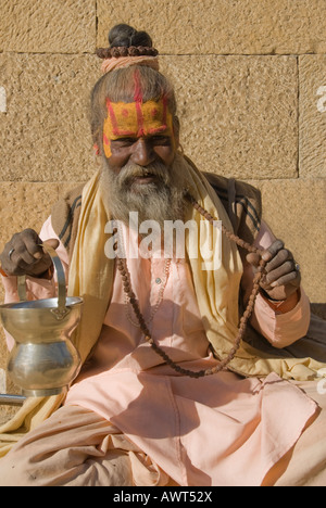 Portrait of an elderly sadhu with beads and bronze bowl dressed in pastel robe in Jaisalmer, Rajasthan, India - Stock Photo