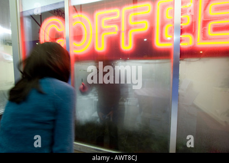 A woman peers inside a steamy coffee shop window, with a neon Coffee sign in the forground. - Stock Photo