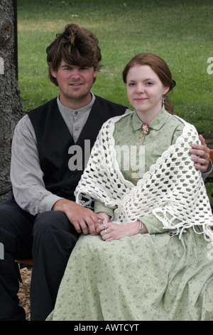 A young couple sitting together at a western reenactment - Stock Photo