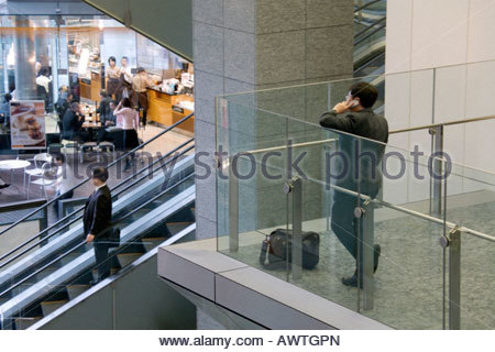 businessman talking on his cellphone in the lobby of a large office building - Stock Photo