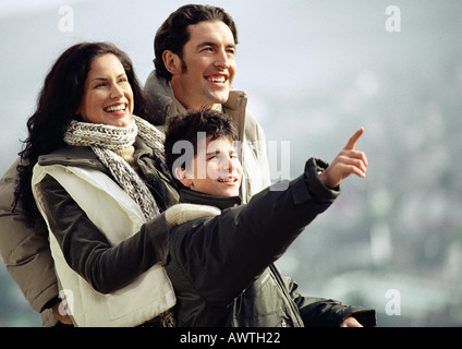 Adult man and woman with boy, warmly dressed, boy pointing and adults looking in direction that boy is pointing,waist - Stock Photo