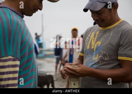 Men trading exchange money for fish Puerto Lopez fishing Harbour Ecuador South America. market - Stock Photo