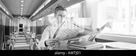 Businessman sitting in train reading newspaper, b&w, panoramic view - Stock Photo