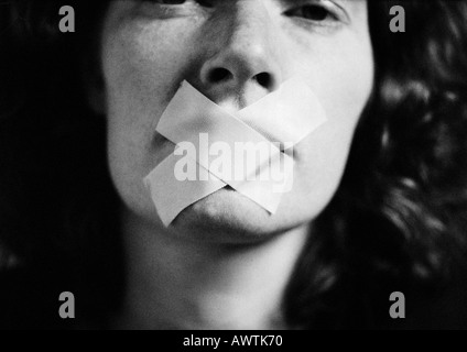 Woman with tape over mouth, close-up, blurred - Stock Photo