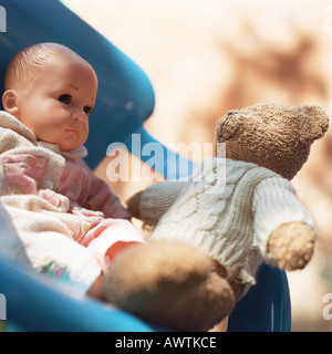 Teddy bear sitting in chair with baby doll - Stock Photo