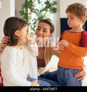 Woman with arms around two children, looking at girl blowing nose - Stock Photo