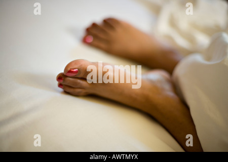 Feet in white sheets - Stock Photo