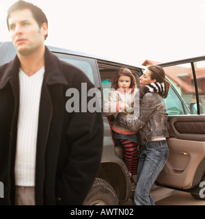 Mother getting daughter out of car, father walking - Stock Photo