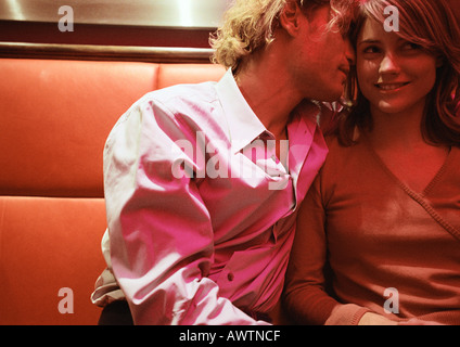 man whispering into woman�s ear stock photo royalty free