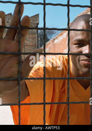 Man behind fence, close-up - Stock Photo