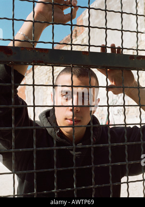 Man standing behind fence, looking at camera, portrait - Stock Photo