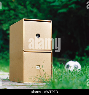 Cardboard drawers on ground, soccerball in background - Stock Photo