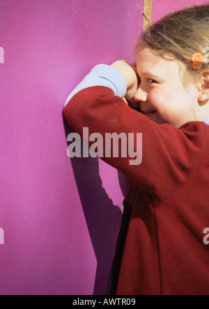 Little girl playing hide-and-seek, peeking sideways at camera - Stock Photo