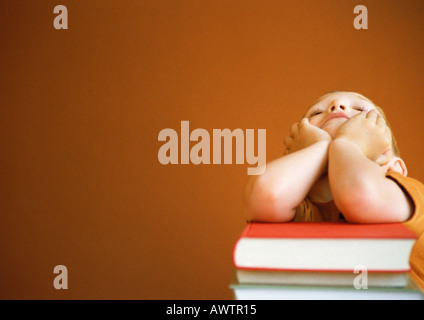 Little boy leaning on stack of books, head in hands - Stock Photo