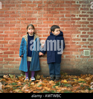 Boy and girl holding hands and making faces in front of brick wall, full length - Stock Photo