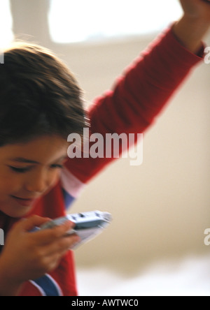 Young boy playing video game, close up, blurred - Stock Photo
