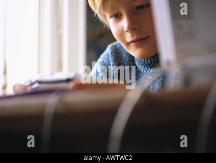 Young boy looking at video game, close up, computer and desk blurred in foreground - Stock Photo