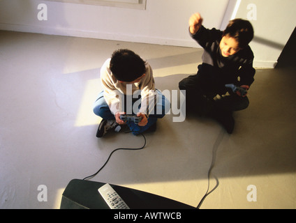 Young boys sitting on floor playing video game, high angle view - Stock Photo