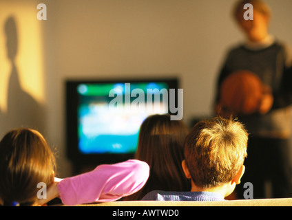 Young boys and girls watching TV, boy in distance blurred - Stock Photo