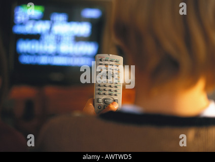 Young boy with remote in hand watching TV, rear view, close up - Stock Photo