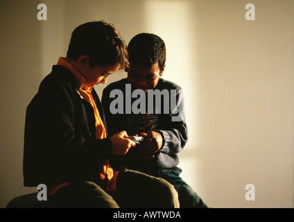 Young boys sitting and looking at video game - Stock Photo