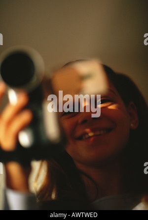 Young girl with camera, smiling, close up - Stock Photo