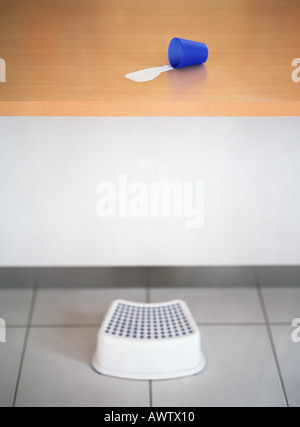 Step stool in front of counter with spilled milk and cup - Stock Photo
