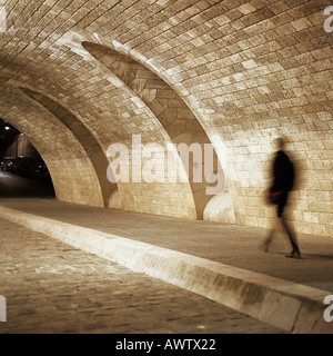 Person walking through tunnel at night - Stock Photo