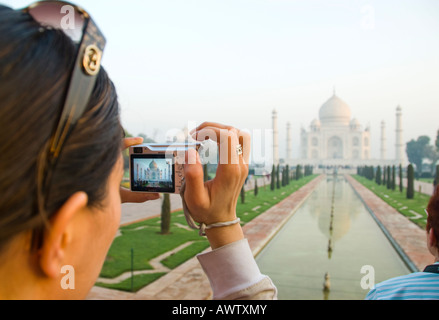 A tourist takes a photograph of the Taj Mahal in Agra India - Stock Photo
