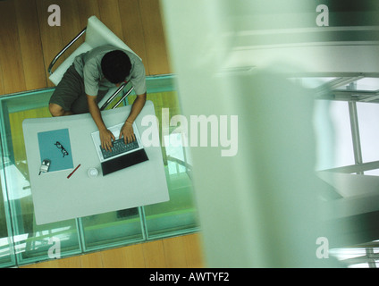 Man sitting at table, working on computer, view from above - Stock Photo
