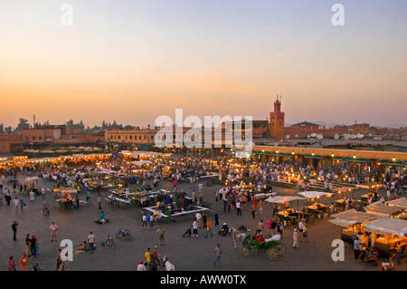 Horizontal wide angle cityscape of the hustle and bustle in the main market square Place Jemaa el Fna at sunset. - Stock Photo