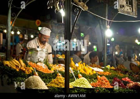 Horizontal close up of a chef preparing food behind mounds of fresh food in Place Jemaa El Fna at night. - Stock Photo