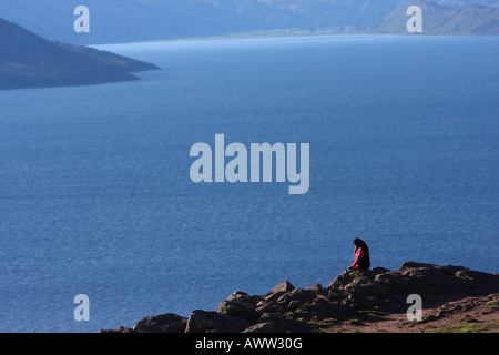 A Quechua girl sits overlooking the view of Lake Titicaca from the traditional Taquille (Taquile) Island, Peru. - Stock Photo
