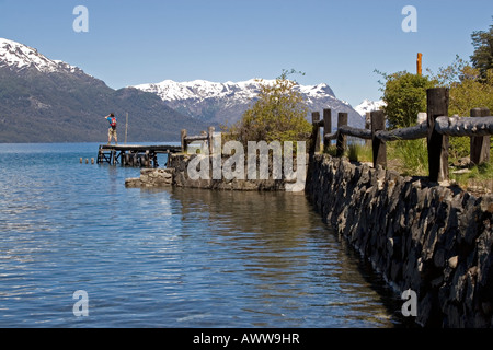 Distant male figure stood on end of lake jetty taking photograph of snow-capped mountains - Stock Photo