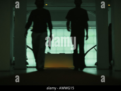 Two people walking through doorway of office, silhouette - Stock Photo