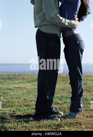 Young couple embracing, waters edge in distance, lower section - Stock Photo